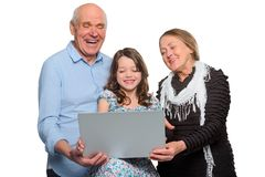 Grandparents and child using notebook. Horizontal photo of family enjoying internet jokes. Grandparents and their child using notebook and laughing at funny royalty free stock photos