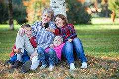 Grandparents with children sitting together and making selfie with cellphone Stock Photos