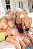 Grandparents com os netos pela piscina Fotografia de Stock Royalty Free