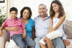 Grandparents com os netos que relaxam em casa T imagens de stock royalty free