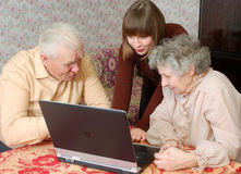 Grandparents e neta que olham ao lapt Fotos de Stock Royalty Free