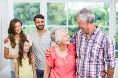 Grandparents embracing while family looking at them Stock Images