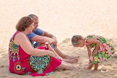 Grandparents enjoying day with granddaughter while blowing soap bubbles on the beach near the sea royalty free stock images