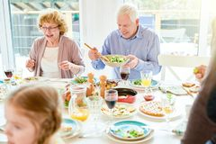 Grandparents Enjoying Food at Family Reunion. Portrait of happy family enjoying dinner together sitting round festive table with delicious dishes, focus two royalty free stock photography
