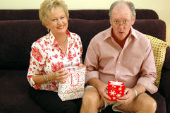 Grandparents with gifts. A senior man and woman with christmas gifts royalty free stock images