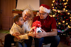 Grandparents giving gifts grandson at Christmas eve Royalty Free Stock Image
