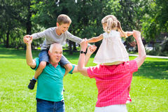 Grandparents Giving Grandchildren Piggyback Ride In Park. Happy Old Grandparents Enjoy Fun Piggyback Ride With Grandchildren Together In Park Royalty Free Stock Image