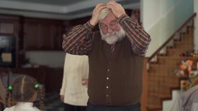 Grandparents grabs their head becouse can`t reassure their naughty running granddaughters, very are angry and tired. Grandparents are trying to reassure their stock video footage