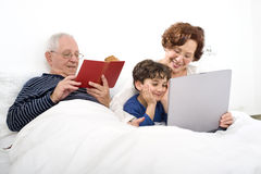 Grandparents grandchild bed laptop Stock Photo