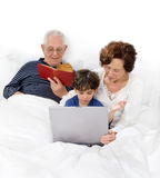 Grandparents grandchild bed laptop Royalty Free Stock Images