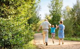 Grandparents and grandchild jumping outdoors. Back view of grandparents and grandchild jumping on a nature path royalty free stock image