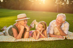 Grandparents with grandchild lying outdoors. Royalty Free Stock Image
