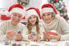 Grandparents with grandchild preparing for Christmas together. Portrait of happy grandparents with grandchild preparing for Christmas together stock photography