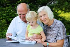 Grandparents with grandchild watching photo album Royalty Free Stock Images