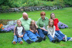 Grandparents and grandchildren. Middle aged adults sit in a park with their grandchildren royalty free stock photography