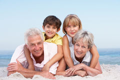 Grandparents And Grandchildren On Beach Holiday. Grandparents And Grandchildren Relaxing On Beach Holiday royalty free stock photography