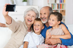 Grandparents and grandchildren with a camera. Grandparents and grandchildren sitting together in a close group on a sofa laughing and doing a self portrait with