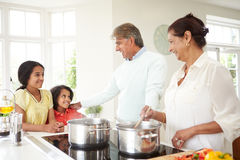 Grandparents And Grandchildren Cooking Meal At Home. In Kitchen Smiling To Each Other stock photography