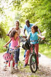 Grandparents With Grandchildren On Cycle Ride In Countryside. Having A Good Time Smiling stock photography