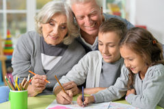 Grandparents and grandchildren drawing. Portrait of happy grandparents and grandchildren drawing together royalty free stock photos