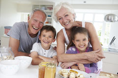 Grandparents With Grandchildren Eating Breakfast In Kitchen Royalty Free Stock Images
