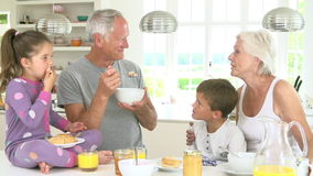 Grandparents With Grandchildren Eating Breakfast In Kitchen stock footage