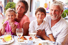 Grandparents With Grandchildren Eating Meal At Restaurant stock photos