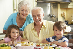 Grandparents And Grandchildren Eating Meal Together In Kitchen Stock Photos