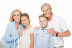 Grandparents with grandchildren embracing. Happy grandparents with grandchildren embracing and smiling at camera isolated on white royalty free stock photography
