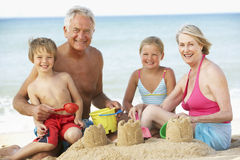 Grandparents And Grandchildren Enjoying Beach Holiday Stock Photos