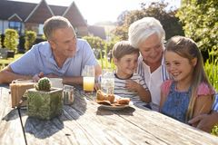 Grandparents With Grandchildren Enjoying Outdoor Summer Snack At Cafe stock images