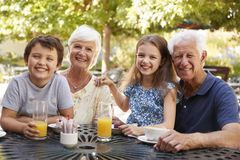 Grandparents And Grandchildren Enjoying Snack At Outdoor Caf� royalty free stock photography