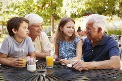 Grandparents And Grandchildren Enjoying Snack At Outdoor Caf� stock image