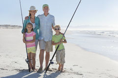 Grandparents and grandchildren with fishing rods on sunny beach stock images