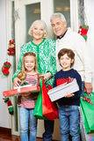 Grandparents with grandchildren and gifts at christmas Stock Images