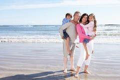 Grandparents And Grandchildren Having Fun On Beach Holiday. Smiling To Camera stock photo