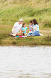 Grandparents And Grandchildren Having Picnic On Riverbank Stock Image