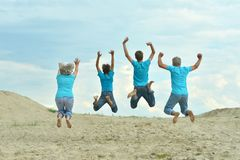 Grandparents with grandchildren jumping. On the beach,view from the back Royalty Free Stock Images