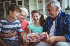 Grandparents and grandchildren looking at surprise gift in living room Royalty Free Stock Image
