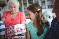 Grandparents and grandchildren looking at surprise gift in living room Royalty Free Stock Images