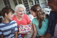 Grandparents and grandchildren looking at surprise gift in living room Stock Image