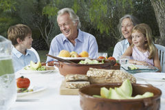 Grandparents With Grandchildren At Outdoor Table Stock Images