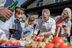 Grandparents and grandchildren preparing food on picnic outdoors. Happy grandparents and grandchildren preparing food on picnic outdoors stock photography