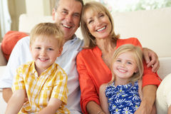 Grandparents With Grandchildren Relaxing. On Sofa At Home Royalty Free Stock Image