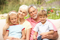 Grandparents And Grandchildren Relaxing In Garden Royalty Free Stock Images