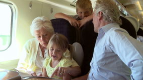 Grandparents And Grandchildren Relaxing On Train Journey Stock Photography
