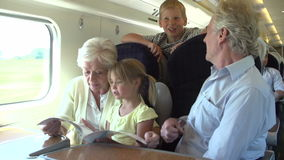 Grandparents And Grandchildren Relaxing On Train Journey stock video