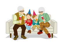 Grandparents and grandchildren sit on the sofa Stock Images