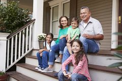 Grandparents With Grandchildren Sit On Steps Leading Up To Home stock photography