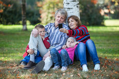 Grandparents with grandchildren sitting together and making selfie with cellphone in park Royalty Free Stock Photos